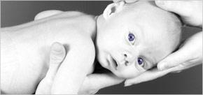 Unas manos de adulto sujetan a un recién nacido sano